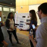 Students discussing research poster